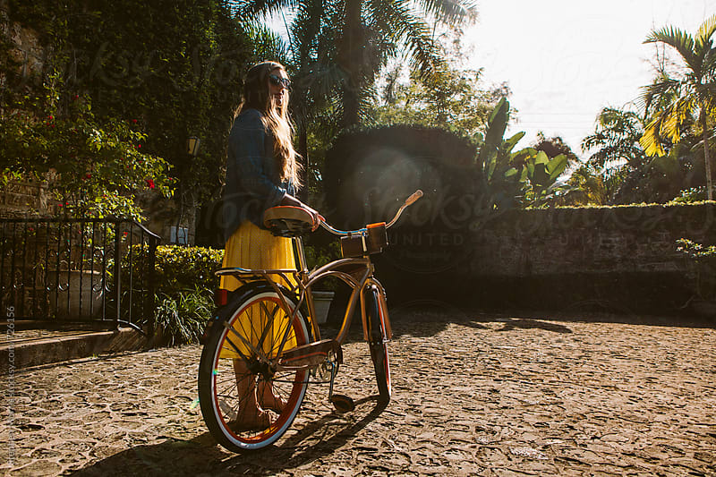 Woman in skirt with bicycle by Stephen Morris for Stocksy United