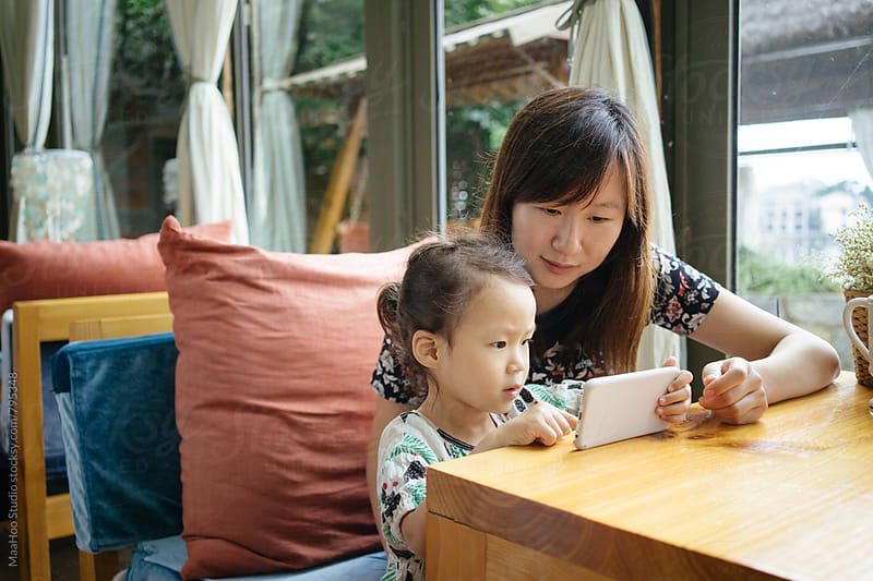 Toddler girl and her young mother using smartphone by MaaHoo Studio for Stocksy United