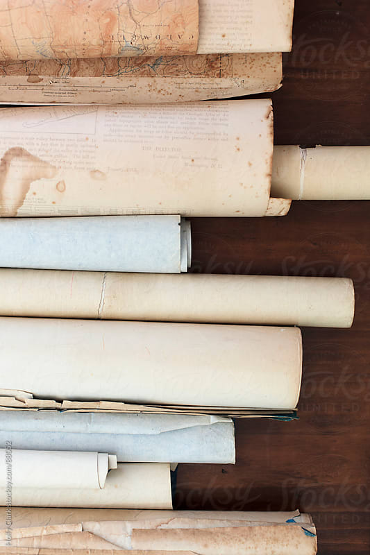 A row of antique scrolls on a table. by Holly Clark for Stocksy United