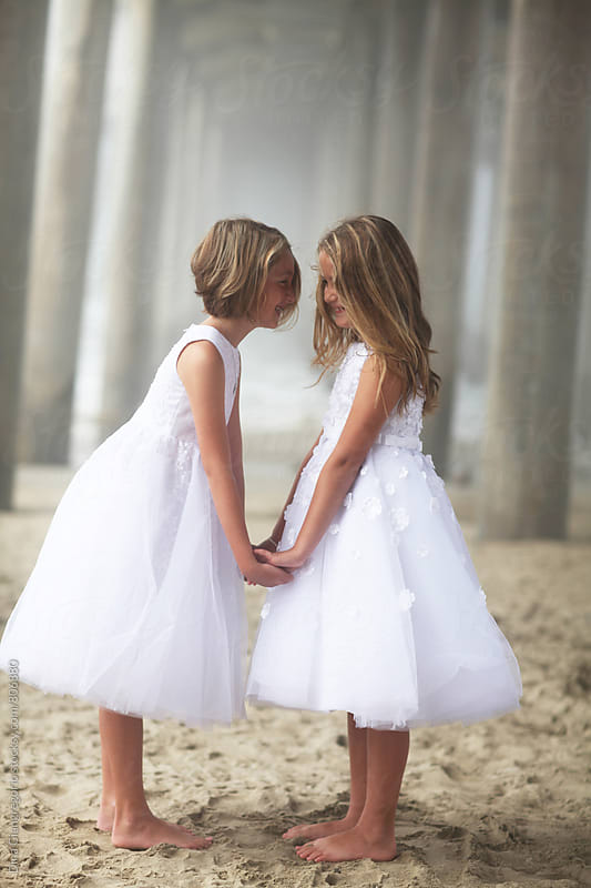 Twin Girls on the beach In Formal White Dresses by Dina Giangregorio for Stocksy United