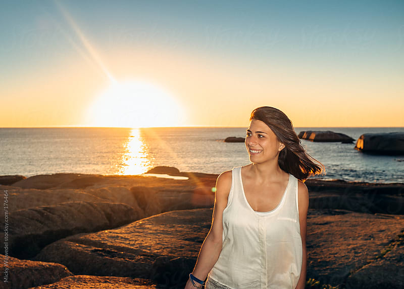 Woman at sunset on a rocky shore by Micky Wiswedel for Stocksy United