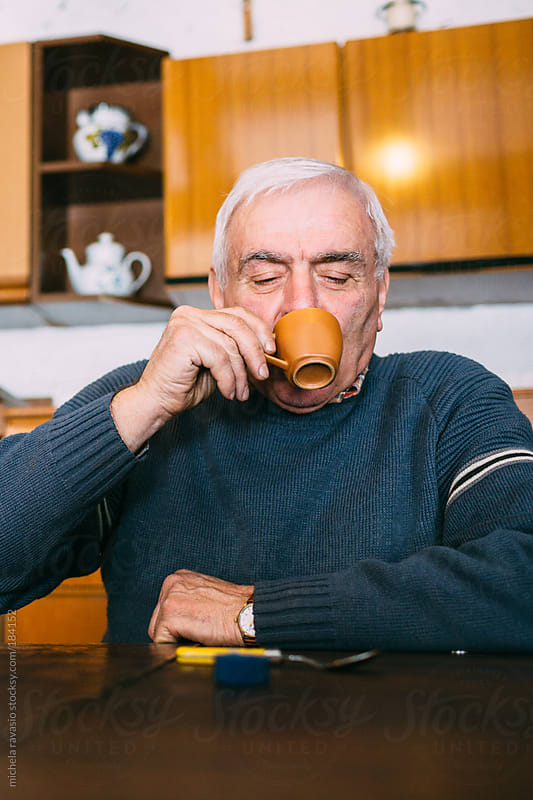 Old man drinking a coffee by michela ravasio for Stocksy United