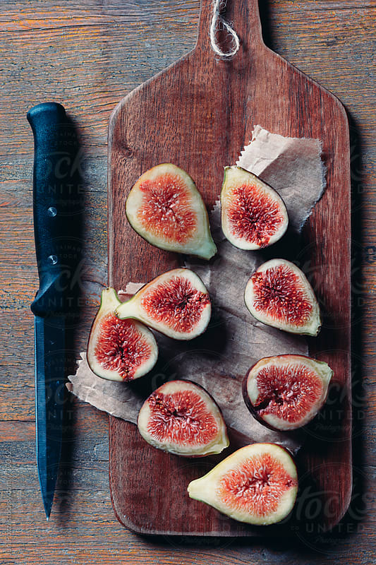 sliced figs on a cutting board by Juri Pozzi for Stocksy United