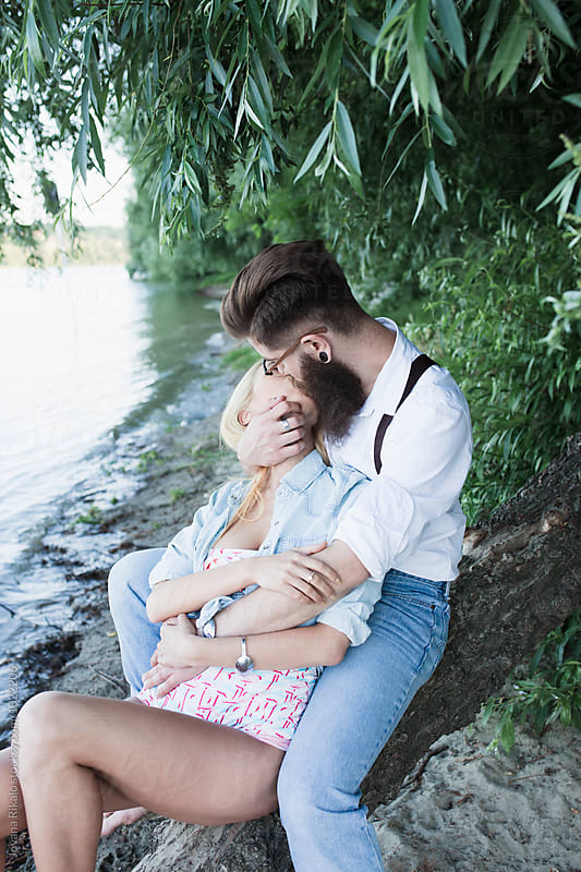 Happy couple kissing on the beach by Jovana Rikalo for Stocksy United