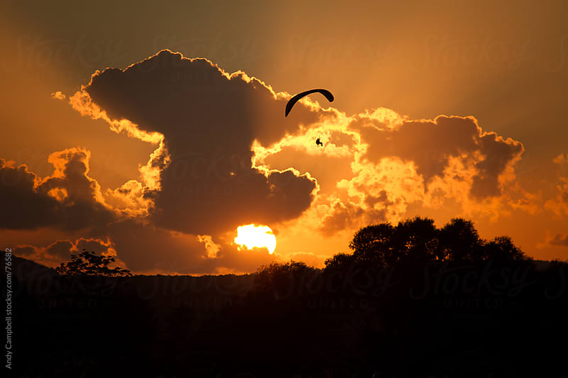 An adventurous paraglider pilot flying into the sunset by Andy Campbell for Stocksy United