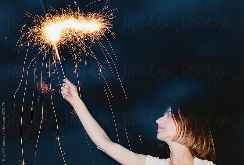 Woman posing with burning sparkler in night  by Sergey Filimonov for Stocksy United