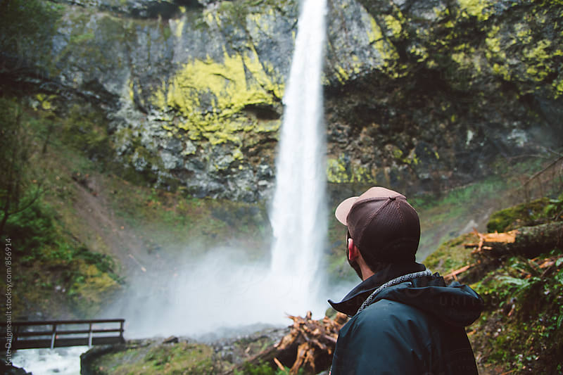 Young man exploring a waterfall on a hike. by Kate Daigneault for Stocksy United