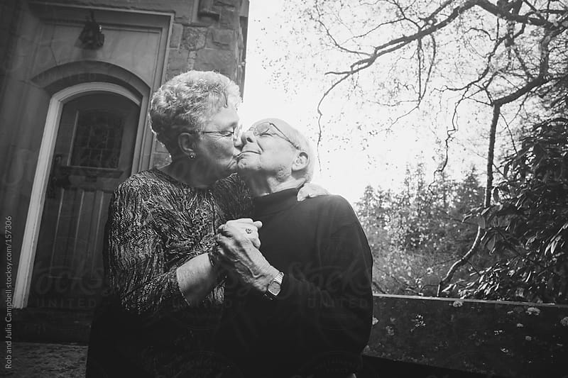 Romantic elderly couple kissing playfully by Rob and Julia Campbell for Stocksy United