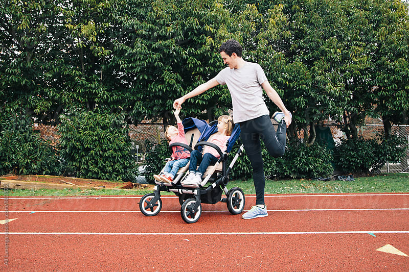 Dad stretching with double stroller by Ali Lanenga for Stocksy United