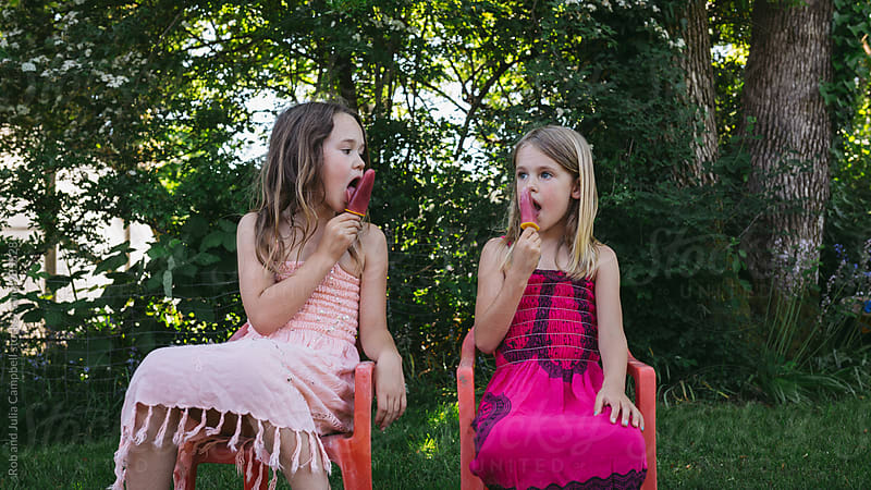 Cute young caucasian girls enjoying popsicle outside in summer by Rob and Julia Campbell for Stocksy United