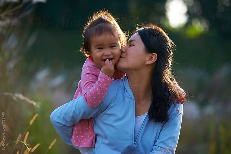 happy little asian girl with her mother outdoor in the autumn sunshine by Bo Bo for Stocksy United