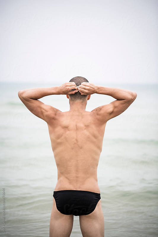 Athlete getting ready for a swim at sea by Lior + Lone for Stocksy United