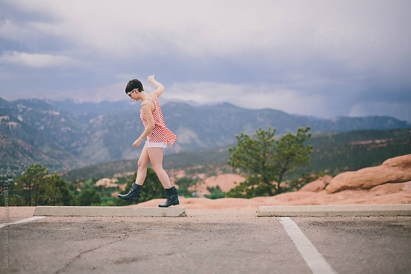 Edgy girl leaping at a parking lot by Gabrielle Lutze for Stocksy United
