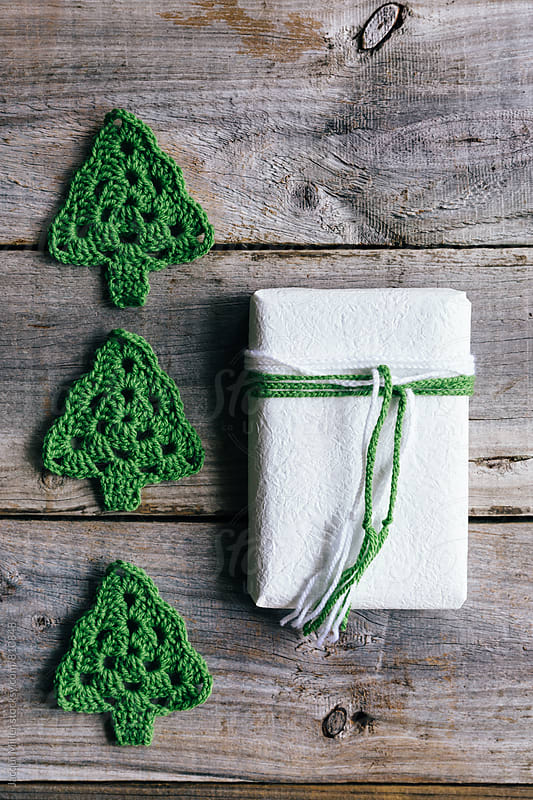 Simple Christmas gift with three crocheted Christmas Trees on rustic wood background  by Jacqui Miller for Stocksy United