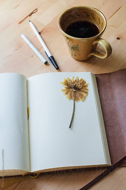 A blank journal lies open on a table next to a cup of coffee, a pen and an e-cigarette. by Holly Clark for Stocksy United