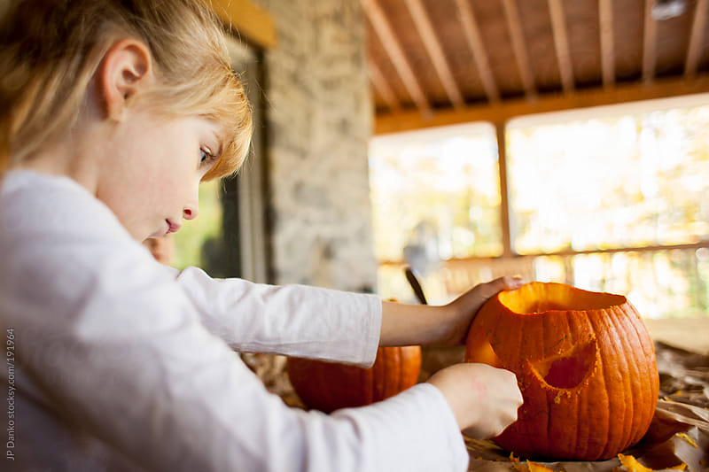 Halloween Pumpkin Carving with Little Girl on Back Porch by JP Danko for Stocksy United