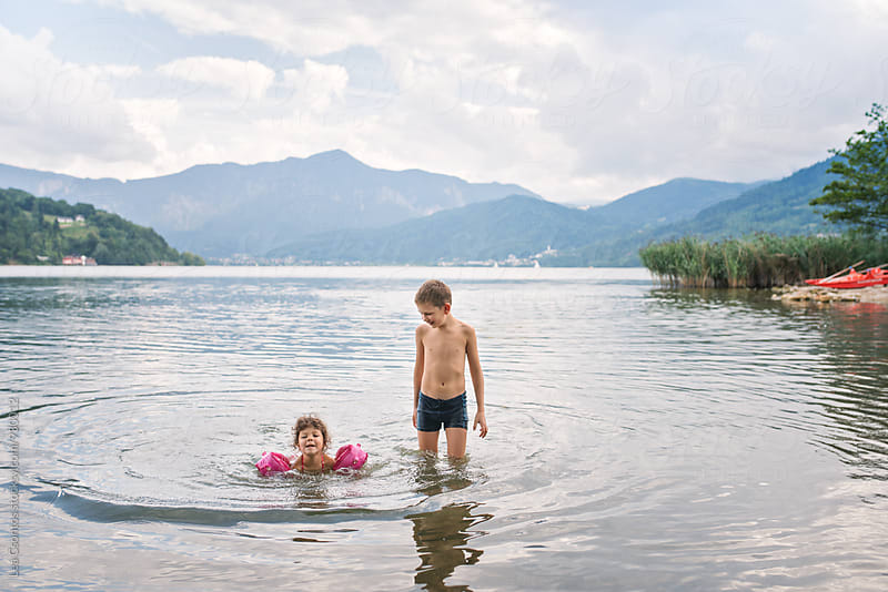 Little girl learning to swim with his brother helping her by Lea Csontos for Stocksy United