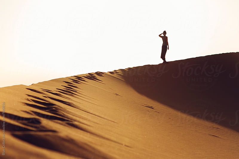 Silhouette woman into the Desert dunes watching the landscape by Jordi Rulló for Stocksy United