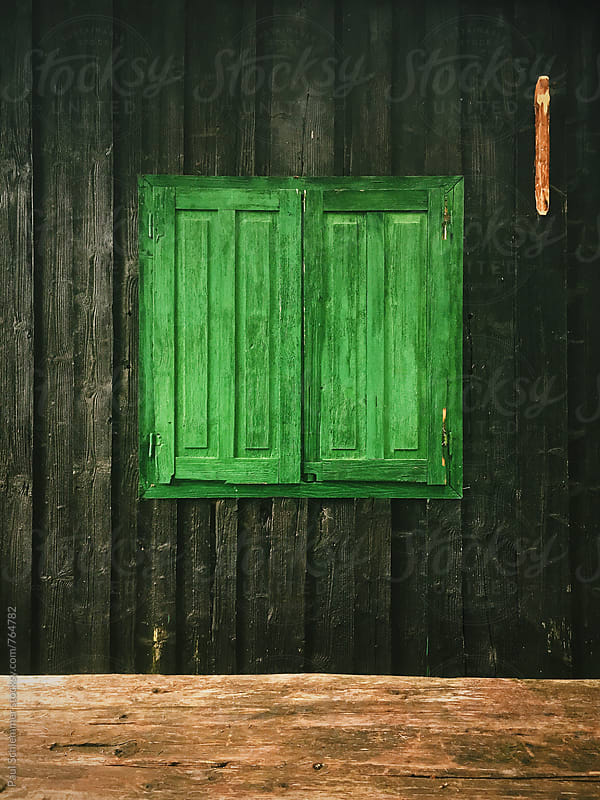 green window on old wooden cabin by Paul Schlemmer for Stocksy United