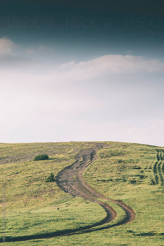 mountain curve  road with a cloudy sky by Javier Pardina for Stocksy United
