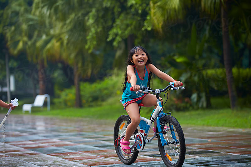 little asian girl riding bike in the park by Bo Bo for Stocksy United