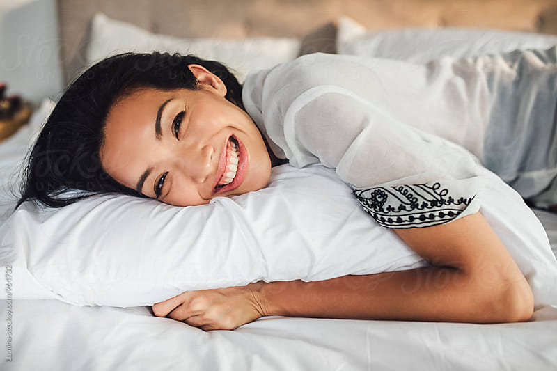 Young Woman Relaxing in Bed by Lumina for Stocksy United