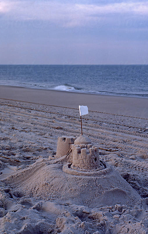 sand castle on beach on Atlantic coast at sunset white flag flying low tide by Ron Mellott for Stocksy United