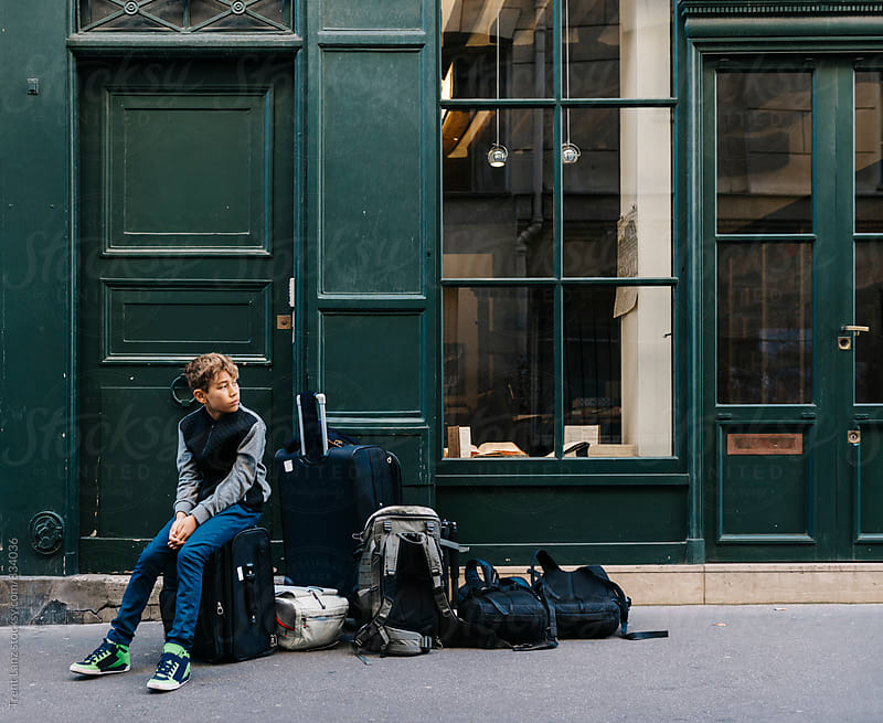 Young handsome boy waiting on travel luggage in the street by Trent Lanz for Stocksy United