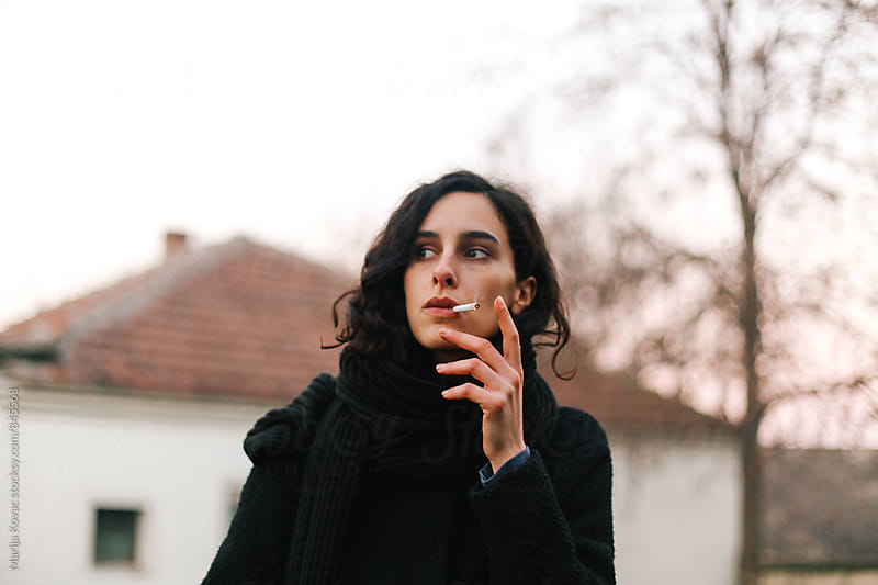 Beautiful brunette woman smoking cigarette by Marija Kovac for Stocksy United
