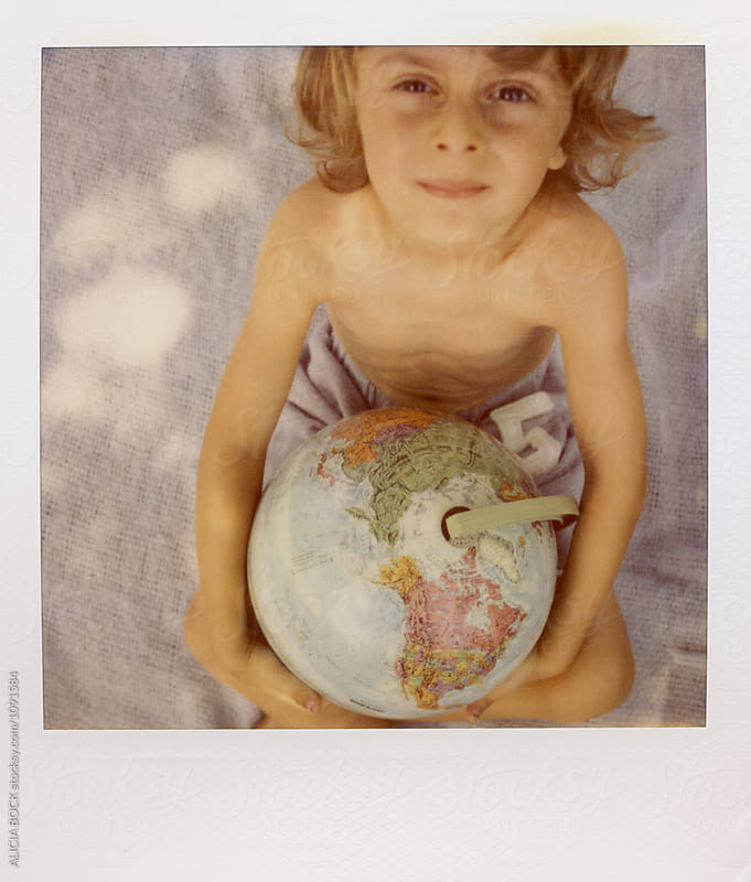 A Boy Holding A Globe On A Summer Day Photographed On Expired Polaroid Film by ALICIA BOCK for Stocksy United