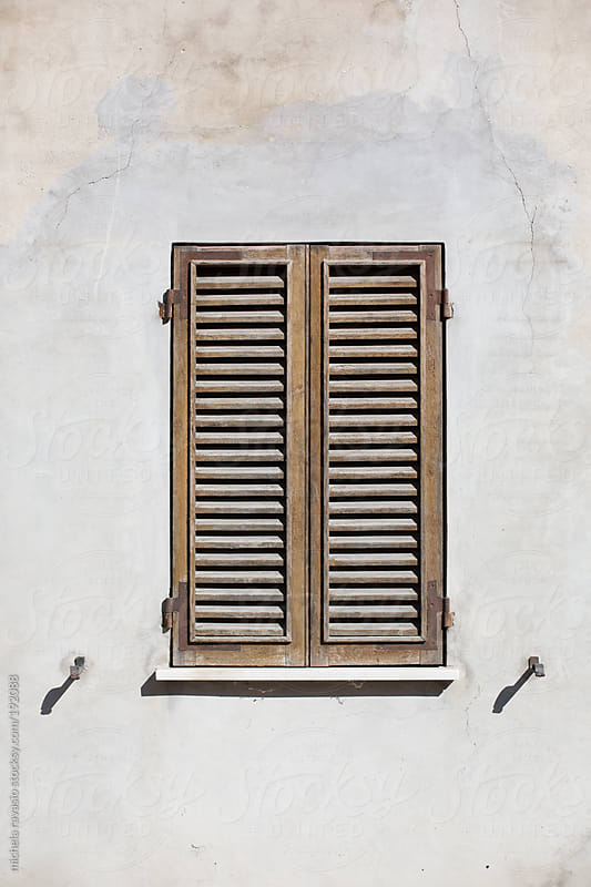 Window with closed shutters in the sun by michela ravasio for Stocksy United