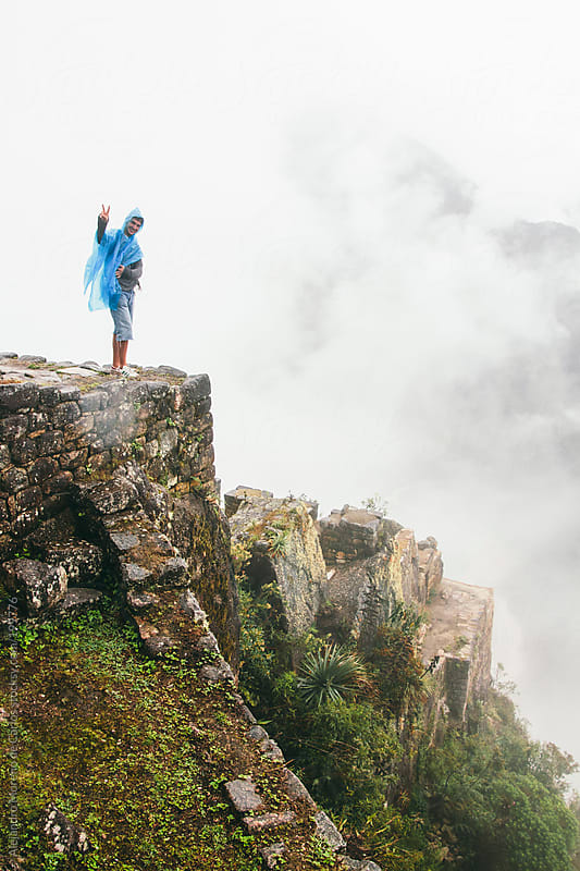 Young happy man on ancient ruins over clouds - Machu Picchu, Peru by Alejandro Moreno de Carlos for Stocksy United