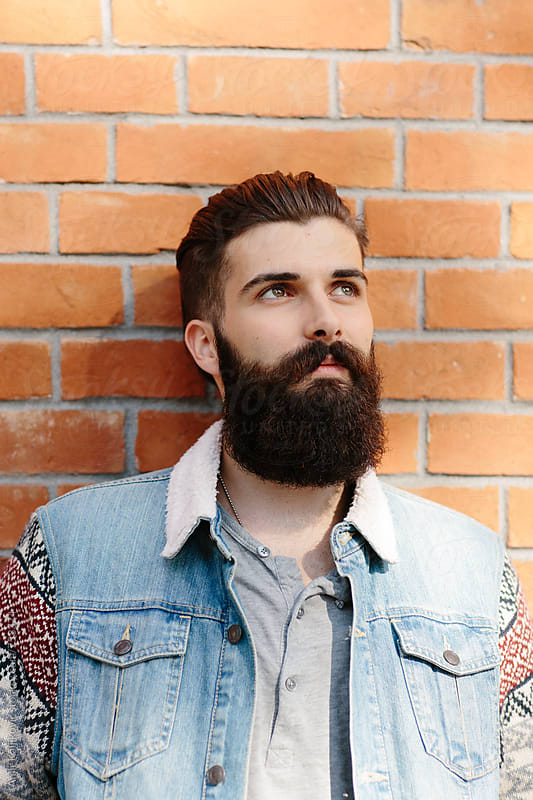 Young Bearded Man Leaning Against Brick Wall by Amir Kaljikovic for Stocksy United