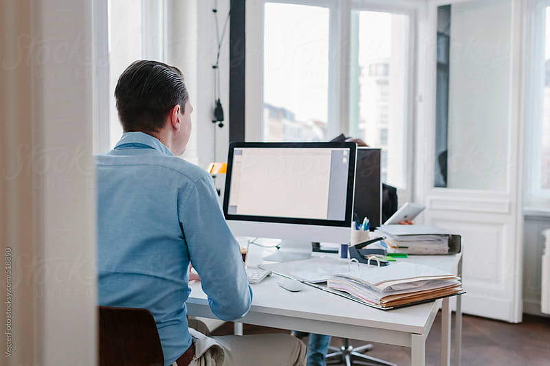 Young Businessman Working at his Desk  by VegterFoto for Stocksy United