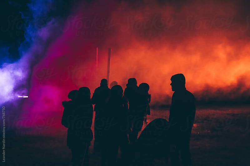 silhouettes of people in front of a colorful smoke by Leander Nardin for Stocksy United
