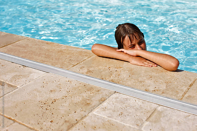 Young boy resting on the edge of the pool  by Bratislav Nadezdic for Stocksy United