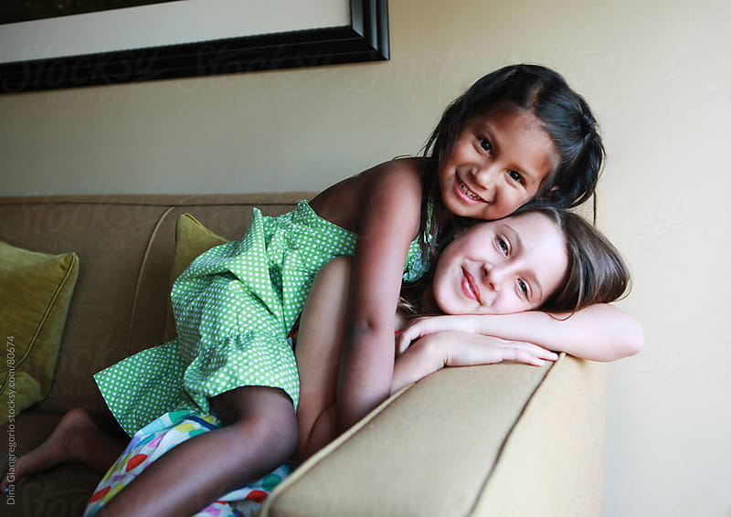 Multiethnic young girls hugging on couch  by Dina Giangregorio for Stocksy United