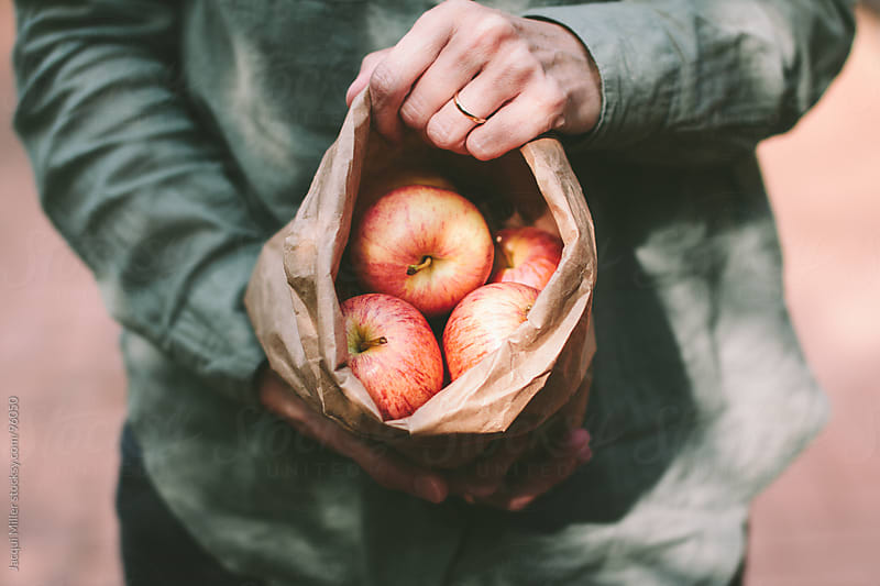 A bag of red apples by Jacqui Miller for Stocksy United