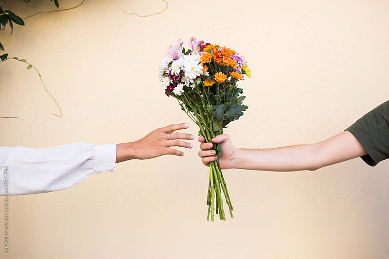 Man giving a woman a bouquet of flowers by michela ravasio for Stocksy United