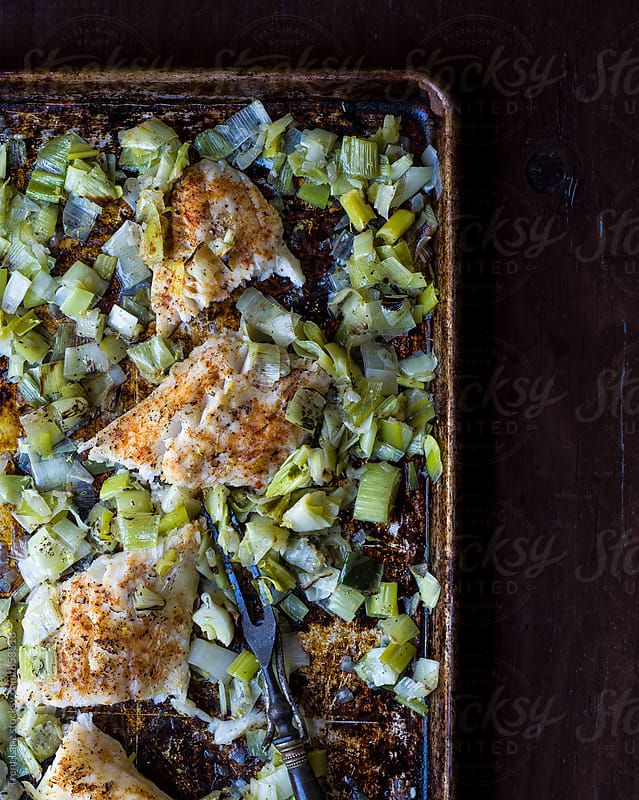 Cooked fish and green onion with leek by Trent Lanz for Stocksy United
