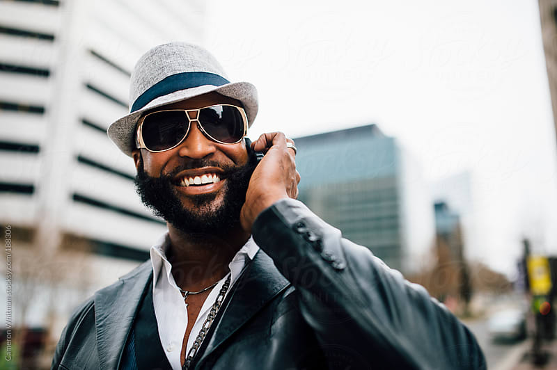 Smiling bearded black man on the phone by Cameron Whitman for Stocksy United