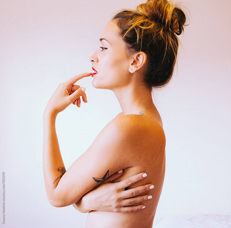 Portrait of beautiful woman in profile covering breast by Susana Ramírez for Stocksy United