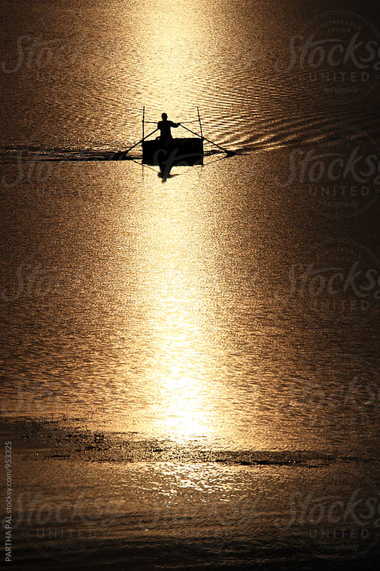 A Person with floating vessel in a lake at evening time by PARTHA PAL for Stocksy United