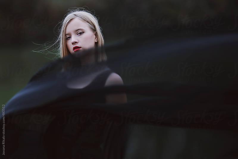 Girl under black scarf on. Windy day. by Jovana Rikalo for Stocksy United