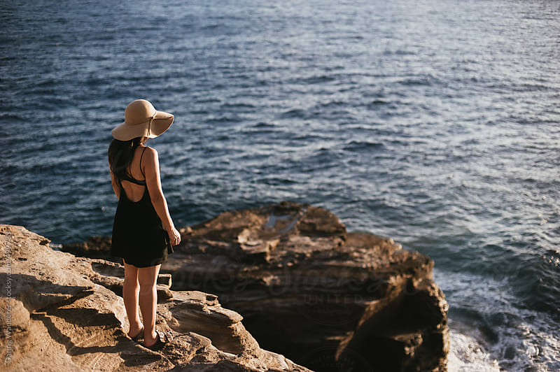 Girl standing on edge of cliff overlooking sunset on Pacific Ocean in Oahu, Hawaii by Daring Wanderer for Stocksy United