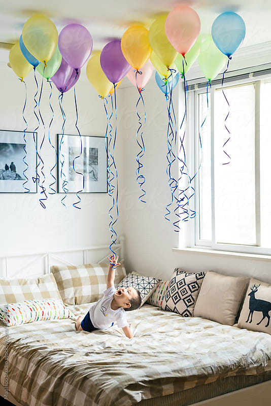 Adorable little boy playing with helium balloons on bed by MaaHoo Studio for Stocksy United