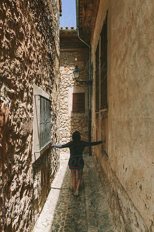 Woman Walking Along a Narrow Rural Street by VICTOR TORRES for Stocksy United
