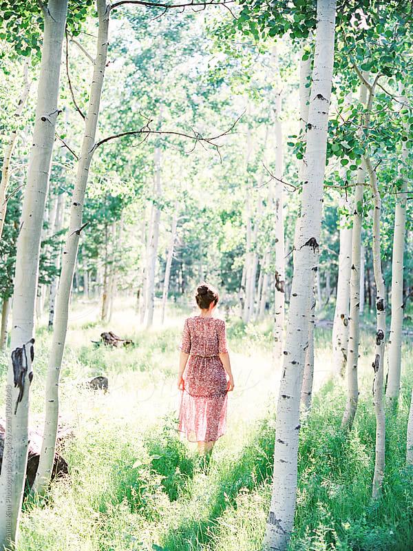 Woman walking in aspen forest by Daniel Kim Photography for Stocksy United