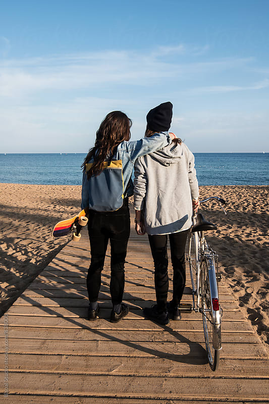 Two young women hanging out in Barcelona beach by Bisual Studio for Stocksy United