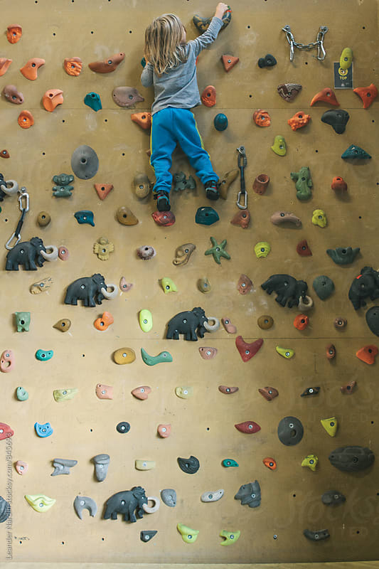 young child on top of an indoor climbing wall by Leander Nardin for Stocksy United